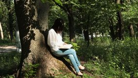 Girl sitting on a tree trunk and reading a book. Sunrise stock footage