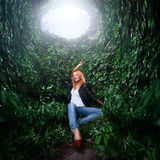 Girl sitting in tunnel from plants Stock Images