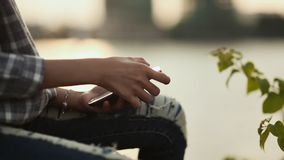 The girl is sitting and typing a message on her smartphone at sunset in the city center. The girl is sitting and typing a message on her smartphone at sunset in stock footage