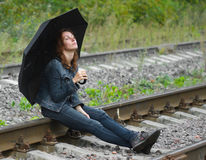 Girl sitting umbrella railway Royalty Free Stock Images