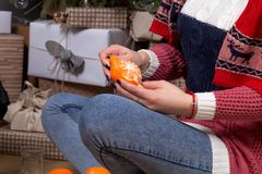 Girl sitting under a Christmas tree on a background of gifts skinning a mandarin. Girl dressed in sweater and scarf on a background of Christmas trees and gifts Royalty Free Stock Images