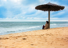 Girl sitting under sunshade looking afar the seas Royalty Free Stock Photography