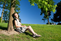 Girl sitting under the tree. On a sunny day royalty free stock photos