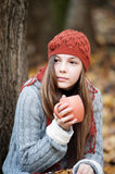 Girl sitting under the tree with a cup in her hands Stock Images