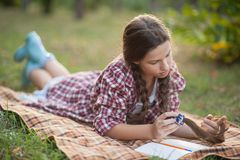The girl sitting under the tree and wrote in Notepad stock photography