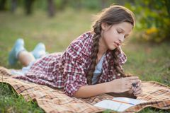 The girl sitting under the tree and wrote in Notepad stock photos