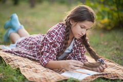 The girl sitting under the tree and wrote in Notepad stock images