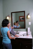 Girl sitting on vanity with older teen Royalty Free Stock Image