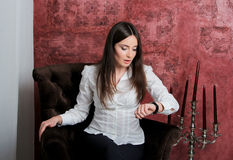 Girl sitting on velvet chair and looking at the watch. stock photo