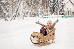Girl sitting in a vintage wooden sled and joyfully throwing their hands Royalty Free Stock Photos