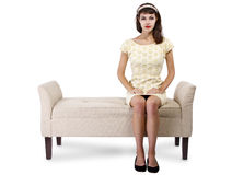 Girl Sitting and Waiting on Chaise Lounge. Stylish retro female sitting on a chaise lounge or sofa on white background stock image