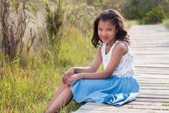 Girl sitting on walkway. Outdoors stock photo