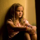 Girl Sitting By A Wall Stock Photography