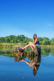 Girl sitting on the water. Girl sitting on an old stump in the middle of the Dnieper River water in summer sunny day Royalty Free Stock Image
