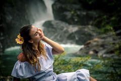 Girl sitting by the waterfall. Beautiful girl in a dress and a Hibiscus flower in her hair sitting by the waterfall, the concept of leisure and travel Stock Image