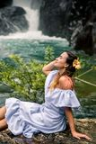Girl sitting by the waterfall. Beautiful girl in a dress and a Hibiscus flower in her hair sitting by the waterfall, the concept of leisure and travel Royalty Free Stock Photography