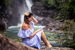Girl sitting by the waterfall. Beautiful girl in a dress and a Hibiscus flower in her hair sitting by the waterfall, the concept of leisure and travel Royalty Free Stock Images