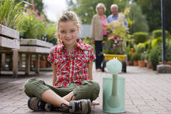 Girl (7-9) sitting with watering can in garden centre, smiling, portrait, grandparents in background Royalty Free Stock Photos