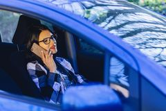 Girl is sitting at wheel of car and talking by phone stock images