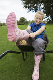 Girl (9-11) sitting in wheelbarrow in field, putting on pink wellington boots, portrait.  Royalty Free Stock Image
