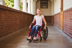 Girl sitting in wheelchair in school corridor Royalty Free Stock Photography