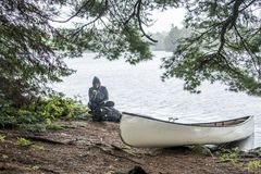 Girl sitting white blank Canoe parked island during Rainy day in Canada Ontario Lake two rivers Algonquin National Park. Rainy day in Canada Ontario Lake two Stock Photos