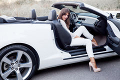 Girl sitting in a white cabriolet with open door Royalty Free Stock Photos