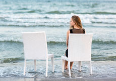 A girl is sitting on a white chair and looking at the sea. The charming young girl is sitting on the background of the sea. stock images