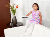 Girl sitting on white sofa in front of television Royalty Free Stock Photography