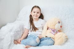 Baby girl sitting on white sofa in white t-shirts and blue jeans. Soft plush banny stock image