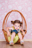 Girl sitting on a wicker basket stock photo