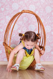 Girl sitting on a wicker basket royalty free stock images