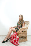 Girl sitting in wicker chair with big red bag Royalty Free Stock Images