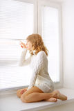 Girl sitting at the window royalty free stock photos