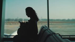 Girl sitting at the window in the airport terminal.  stock video footage
