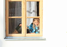 Girl sitting in the window Royalty Free Stock Photos