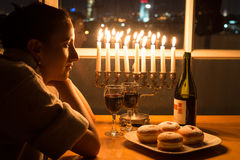 A girl sitting by the window with the menorah celebrating Hanukkah. Stock Images