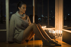 A girl sitting by the window with the menorah celebrating Hanukkah. Royalty Free Stock Images