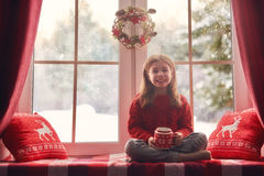 Girl sitting by window Royalty Free Stock Images