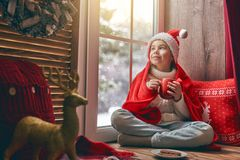 Girl sitting by the window. Merry Christmas and happy holidays! Cute little girl sitting by the window with a cup of warm drink and looking at the winter forest Royalty Free Stock Image