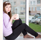 A girl is sitting on the window-sill. A girl with a cup is sitting on the window-sill Stock Image