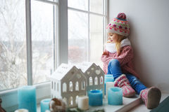 Girl sitting on a window sill Royalty Free Stock Image
