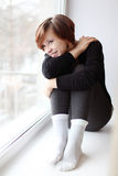 Girl sitting on the window-sill Stock Images