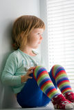 Girl sitting on windowsill, looking out window Royalty Free Stock Photo