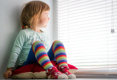 Girl sitting on windowsill, looking out window Royalty Free Stock Images
