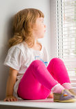 Girl sitting on windowsill, looking out window Royalty Free Stock Photos
