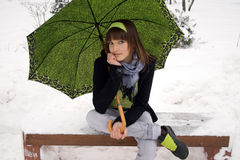 Girl sitting in winter park Stock Photos