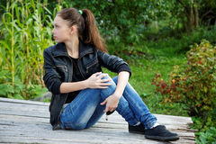 The girl sitting on wooden boards in garden Royalty Free Stock Images
