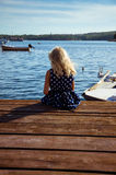 Girl sitting in wooden jetty Stock Photos