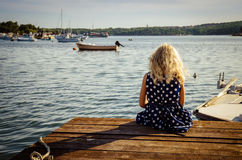 Girl sitting in wooden jetty Stock Photo